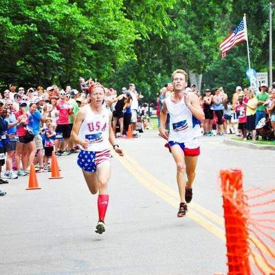 Runners sprinting at the end of the FireKracker 5k elite race.